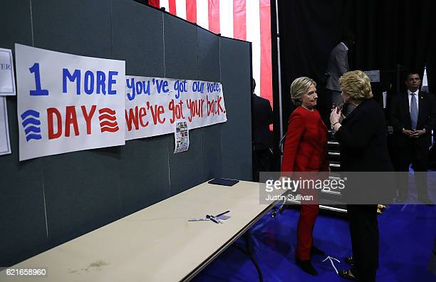 Democratic presidential nominee former Secretary of State Hillary Clinton talks with US Sen Debbie Stabenow backstage after a campaign rally at Grand...