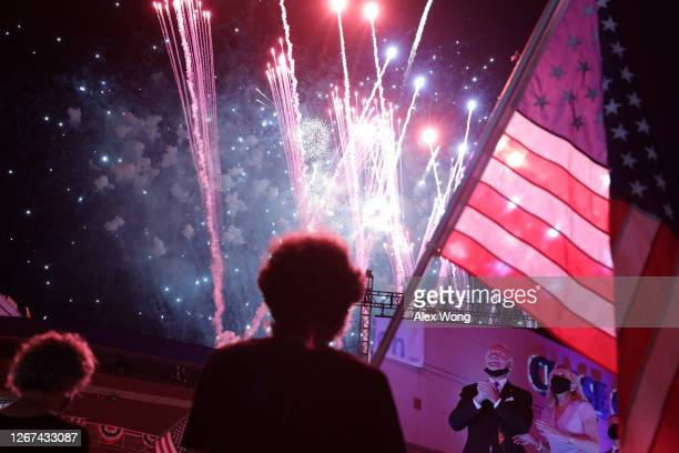 Democratic presidential nominee former Vice President Joe Biden and his wife Jill Biden are seen on a screen as supporters watch fireworks during the...