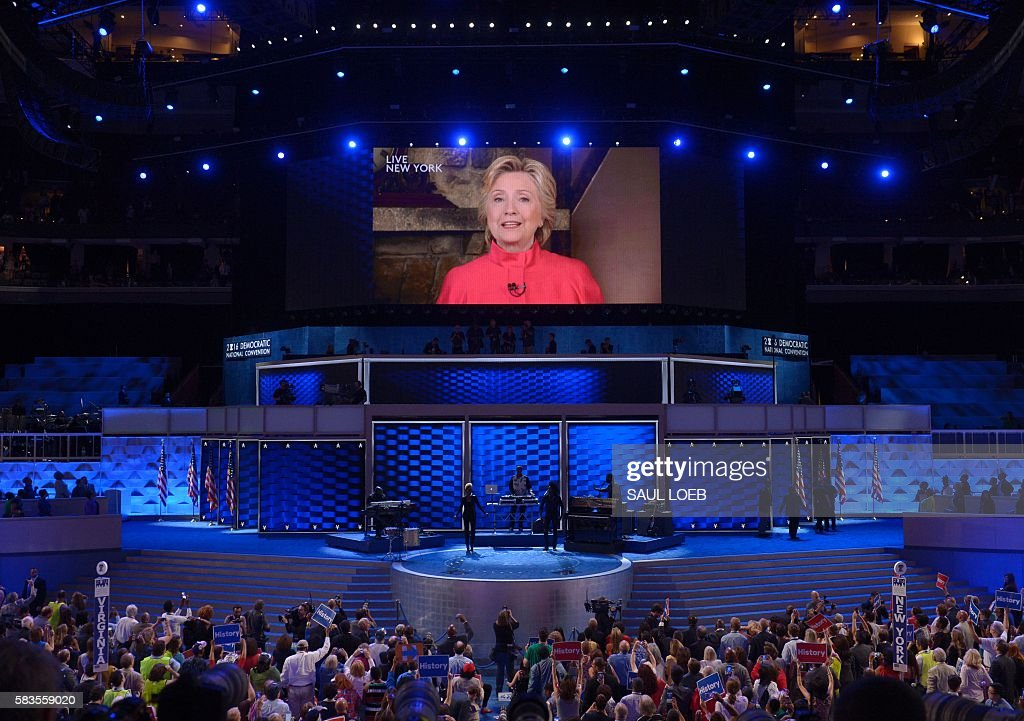 Democratic presidential nominee Hillary Clinton addresses the second evening session of the Democratic National Convention from a screen at the Wells Fargo Center, July 26, 2016 in Philadelphia, Pennsylvania. / AFP / SAUL