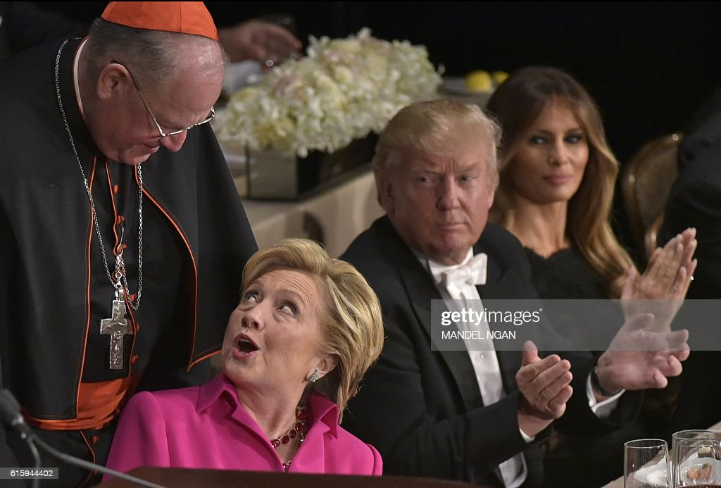 TOPSHOT - Democratic presidential nominee Hillary Clinton (2nd L) and Archbishop of New York Cardinal Timothy Dolan (L) chat watched by Republican presidential nominee Donald Trump and his wife Melania Trump during the 71st annual Alfred E. Smith Memorial Foundation Dinner at the Waldorf-Astoria Hotel in New York on October 20, 2016. / AFP / MANDEL