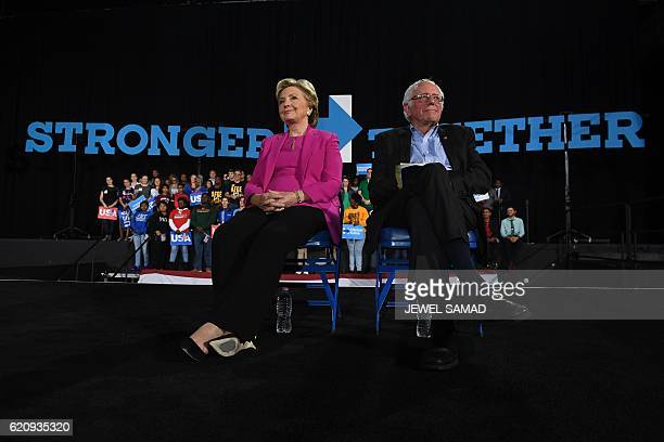 US Democratic presidential nominee Hillary Clinton and Bernie Sanders listen to singer Pharrell Williams during a campaign rally in Raleigh North...