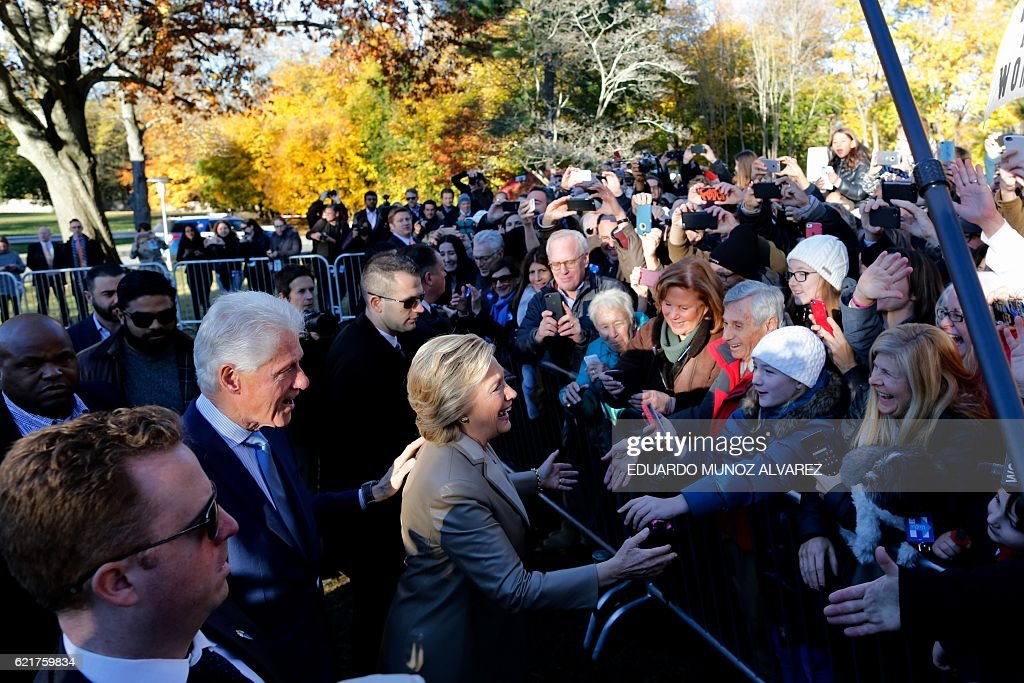 TOPSHOT - Democratic presidential nominee Hillary Clinton (C)and her husband Bill greet supporters after casting her vote in Chappaqua, New York on November 8, 2016. After an exhausting, wild, bitter, and sometimes sordid campaign, Americans finally began voting Tuesday for a new president: either the billionaire populist Donald Trump or Hillary Clinton, seeking to become the first woman to win the White House. / AFP / EDUARDO
