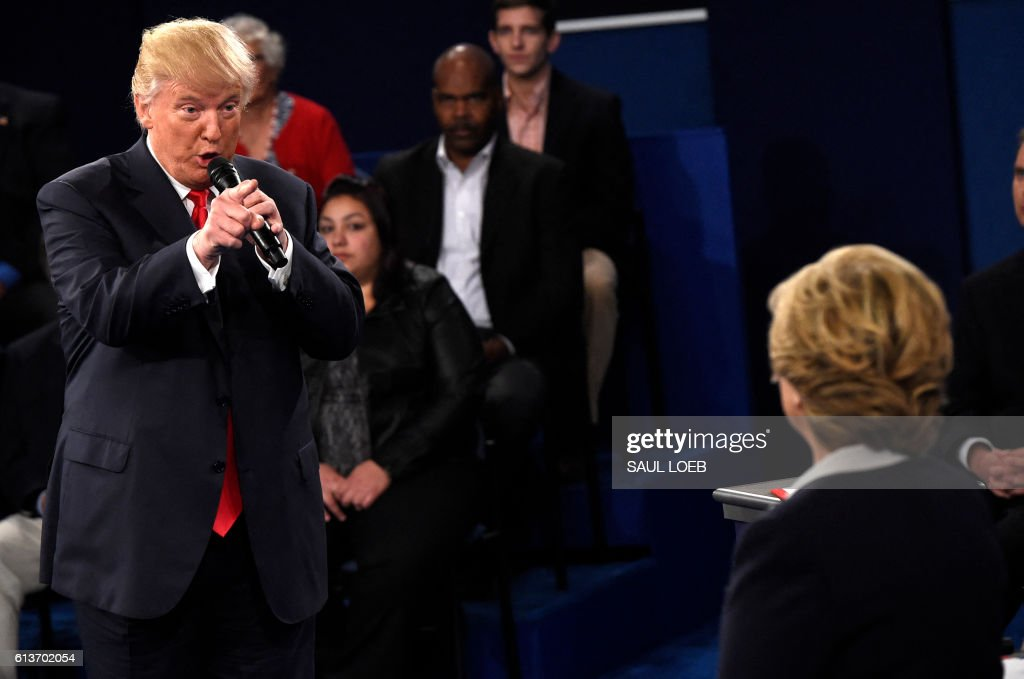 Democratic Presidential nominee Hillary Clinton (R) and Republican Presidential nominee Donald Trump participate a town hall debate against Republican nominee Donald Trump at Washington University in St. Louis, Missouri, on October 9, 2016. /