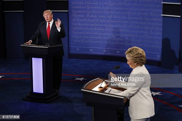 TOPSHOT Democratic presidential nominee Hillary Clinton and Republican presidential nominee Donald Trump speak during the final presidential debate...