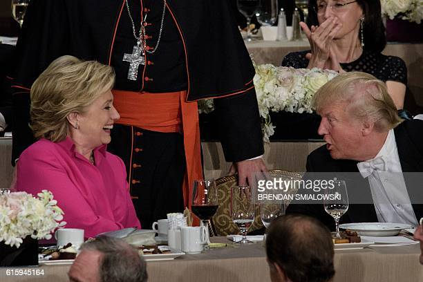 TOPSHOT Democratic presidential nominee Hillary Clinton and Republican presidential nominee Donald Trump shake hands after speaking during the Alfred...