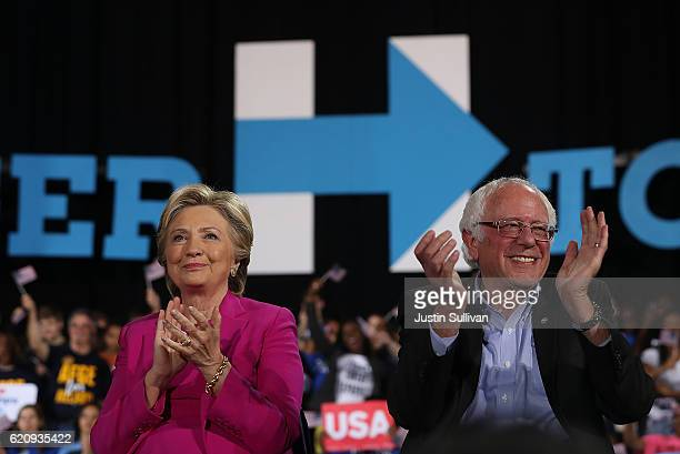 Democratic presidential nominee Hillary Clinton and US Sen Bernie Sanders look on during a campaign rally at Coastal Credit Union Music Park at...
