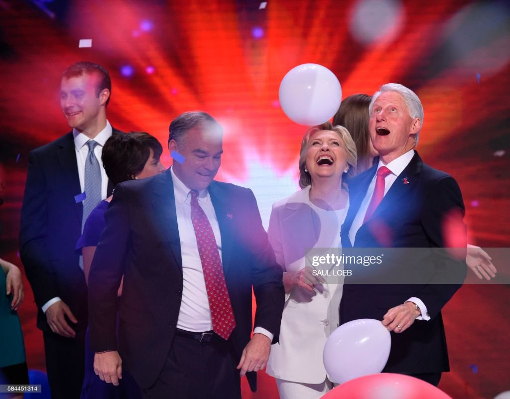 TOPSHOT - Democratic presidential nominee Hillary Clinton (2nd-R) celebrates on stage with husband former US president Bill Clinton (R), running mate Tim Kaine (2nd-L), and son-in-law Marc Mezvinsky (L) on the fourth and final night of the Democratic National Convention at Wells Fargo Center on July 28, 2016 in Philadelphia, Pennsylvania. /