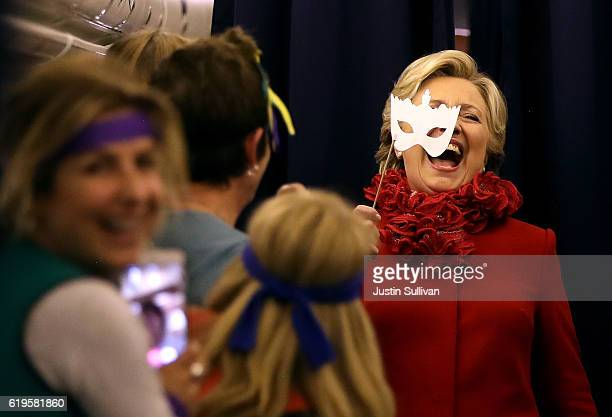 Democratic presidential nominee Hillary Clinton holds a masquerade mask as she jokes with members of her staff aboard her camapign plane on October...