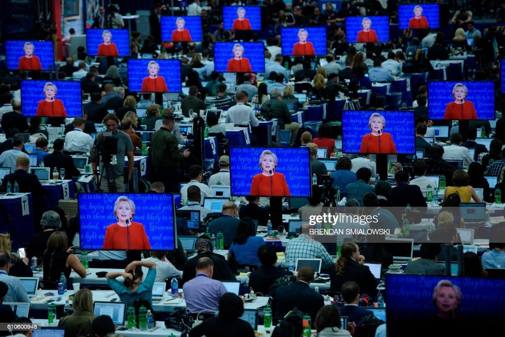 TOPSHOT - Democratic presidential nominee Hillary Clinton is seen on multiple screens speaking during the first US Presidential Debate at Hofstra University September 26, 2016 in Hempstead, New York. / AFP PHOTO / Brendan Smialowski