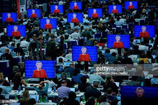 TOPSHOT Democratic presidential nominee Hillary Clinton is seen on multiple screens speaking during the first US Presidential Debate at Hofstra...