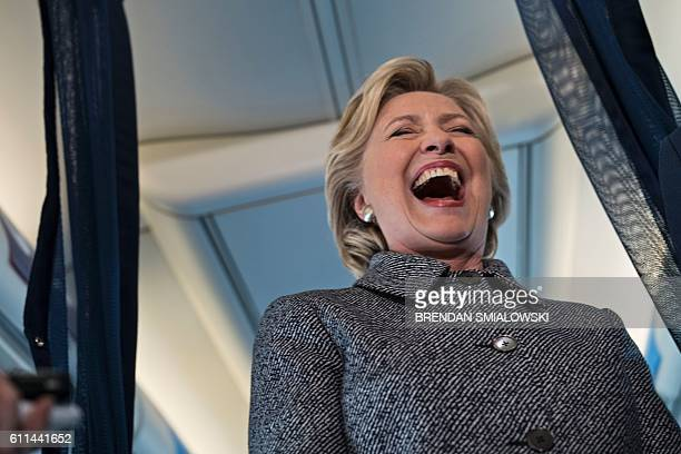 TOPSHOT Democratic presidential nominee Hillary Clinton laughs at a question about her favorite world leader while speaking to the press on her plane...