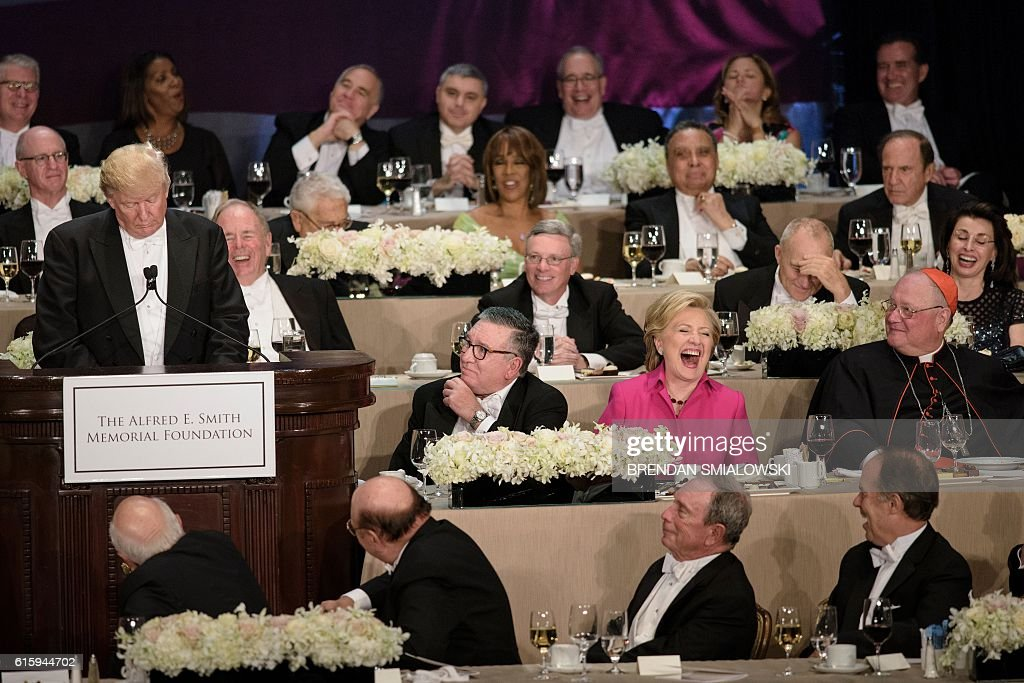TOPSHOT - Democratic presidential nominee Hillary Clinton laughs at as Republican presidential nominee Donald Trump tells a joke during the Alfred E. Smith Memorial Foundation Dinner at Waldorf Astoria October 20, 2016 in New York, New York. / AFP / Brendan Smialowski