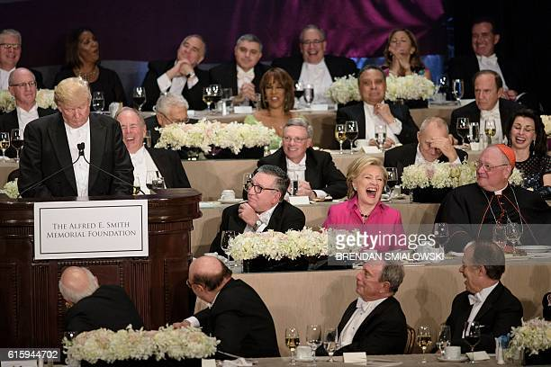 Democratic presidential nominee Hillary Clinton laughs at as Republican presidential nominee Donald Trump tells a joke during the Alfred E. Smith...