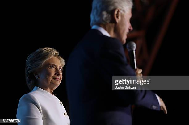 Democratic presidential nominee Hillary Clinton looks on as her husband former US President Bill Clinton speaks during a debate watch party at Craig...