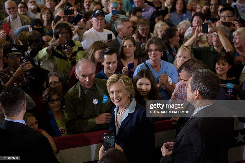 Democratic presidential nominee Hillary Clinton poses for a photo after speaking during an Ohio Democratic Party rally October 3, 2016 in Akron, Ohio. / AFP / Brendan Smialowski