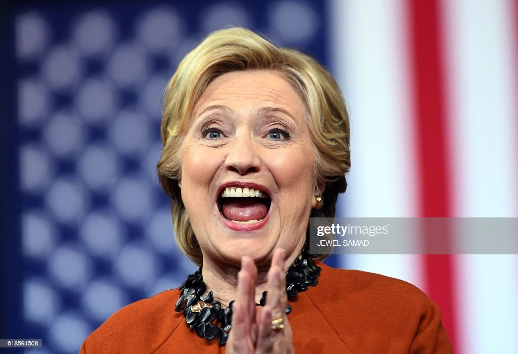 Democratic presidential nominee Hillary Clinton reacts as US First Lady Michelle Obama speaks during a campaign rally in Winston-Salem, North Carolina on October 27, 2016. Michelle Obama, surprise star of the 2016 White House campaign, hit the trail Thursday with Democrat Hillary Clinton as the former and current first ladies fight to conquer battleground states before Election Day. / AFP PHOTO / Jewel SAMAD