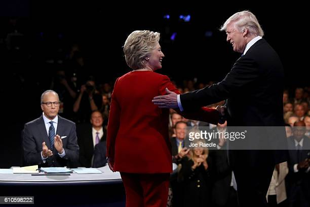 Democratic presidential nominee Hillary Clinton shakes hands with Republican presidential nominee Donald Trump as Moderator Lester Holt looks on...