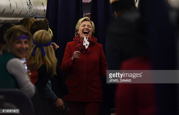 US Democratic presidential nominee Hillary Clinton smiles holding a mask onboard her campaign plane Erlanger Kentucky on October 31 2016 Clinton...