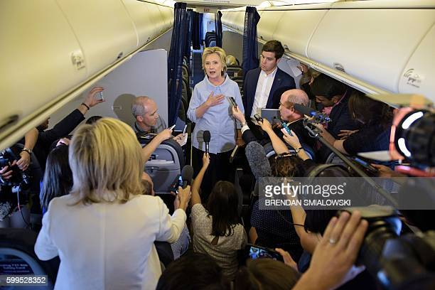 Democratic presidential nominee Hillary Clinton speaks to the press onboard her plane September 5 2016 above Iowa / AFP / Brendan Smialowski