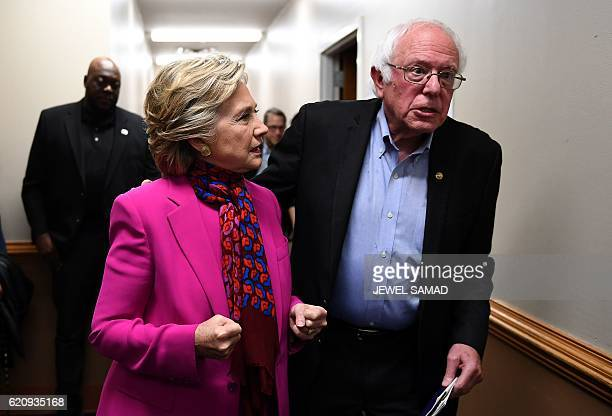 US Democratic presidential nominee Hillary Clinton talks with Bernie Sanders backstage before a campaign rally in Raleigh North Carolina on November...