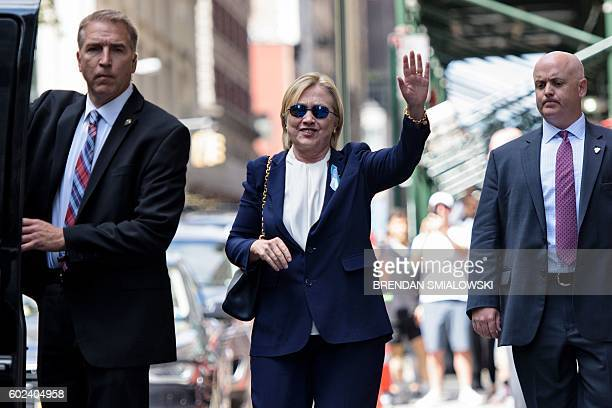 US Democratic presidential nominee Hillary Clinton waves to the press as she leaves her daughter's apartment building after resting on September 11...