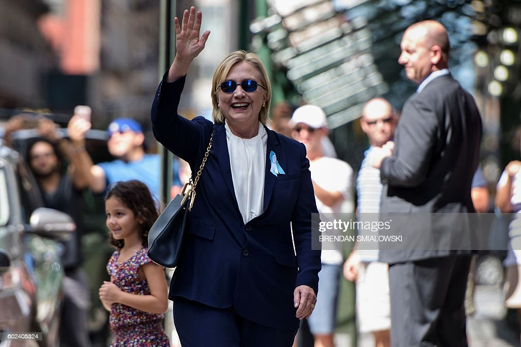 Democratic presidential nominee Hillary Clinton waves to the press as she leaves her daughter's apartment building after resting on September 11, 2016, in New York. Clinton departed from a remembrance ceremony on the 15th anniversary of the 9/11 attacks after feeling 'overheated,' but was later doing 'much better,' her campaign said. / AFP / Brendan Smialowski