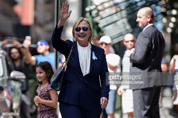 Democratic presidential nominee Hillary Clinton waves to the press as she leaves her daughter's apartment building after resting on September 11 in...