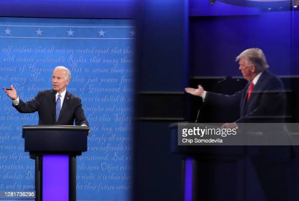 Democratic presidential nominee Joe Biden and U.S. President Donald Trump, shown in a reflection, participate in the final presidential debate at...