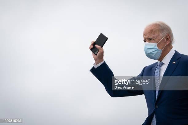 Democratic presidential nominee Joe Biden holds his phone as he arrives at Atlanta International Airport on October 27, 2020 in Atlanta, Georgia....