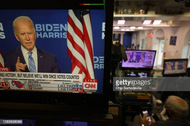 Democratic presidential nominee Joe Biden is seen on televisions in the Brady Press Briefing Room at the White House as he makes a statement about...