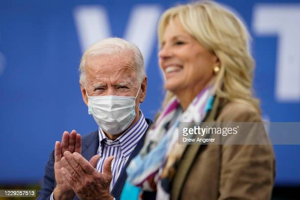 Democratic presidential nominee Joe Biden listens as his wife Dr. Jill Biden speaks during a drive-in campaign rally at Bucks County Community...