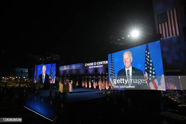 Democratic presidential nominee Joe Biden speaks at a drive-in election night event as Dr. Jill Biden looks on at the Chase Center in the early...