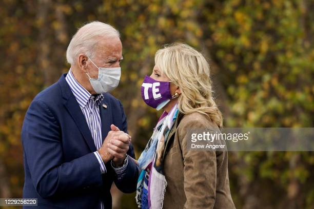 Democratic presidential nominee Joe Biden speaks to his wife Dr. Jill Biden before speaking at a drive-in campaign rally at Bucks County Community...