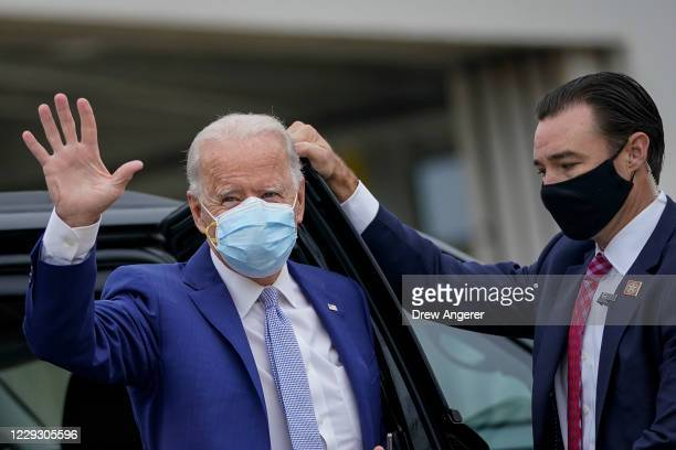 Democratic presidential nominee Joe Biden waves as he arrives to board his campaign plane at New Castle Airport on October 27 2020 in New Castle...
