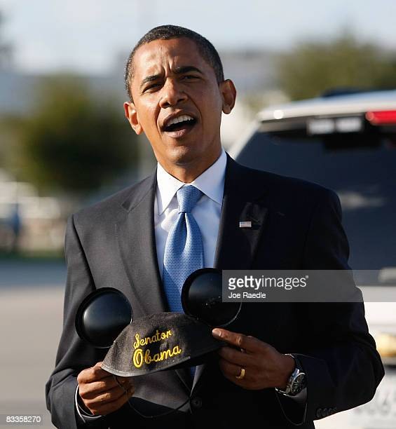 Democratic presidential nominee US Sen Barack Obama holds a pair of Mickey Mouse ears with his name embroidered on them after walking off his plane...