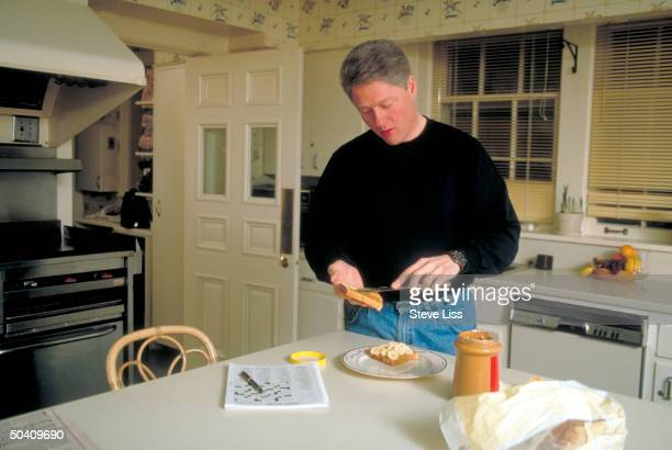 Democratic presidential primary candidate Gov Bill Clinton relaxing at home making peanut butter banana sandwich in kitchen crossword puzzle awaiting...