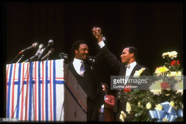 Democratic presidential primary hopeful Jesse Jackson raising hands in victory gesture w Nation of Islam leader Louis Farrakhan during campaign rally
