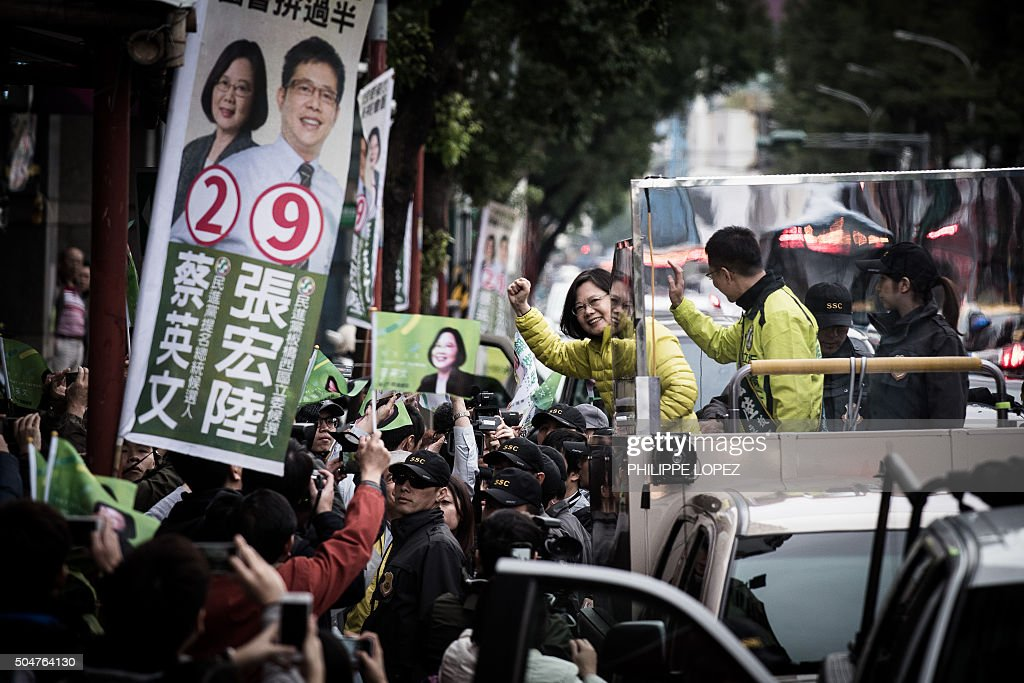 TOPSHOT - Democratic Progressive Party (DPP) presidential candidate Tsai Ing-wen (C) waves to supporters as she campaigns in New Taipei City on January 13, 2016. Taiwan's voters, angry at low salaries and unaffordable housing, are set to elect a new president -- but the island's flagging fortunes and a slowdown in China mean the winner will have a mountain to climb. AFP PHOTO / Philippe Lopez / AFP / PHILIPPE