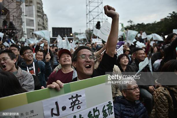 A Democratic Progressive Party supporter gestures with a banner with other gathered supporters after polls closed in Taipei on January 16 2016...