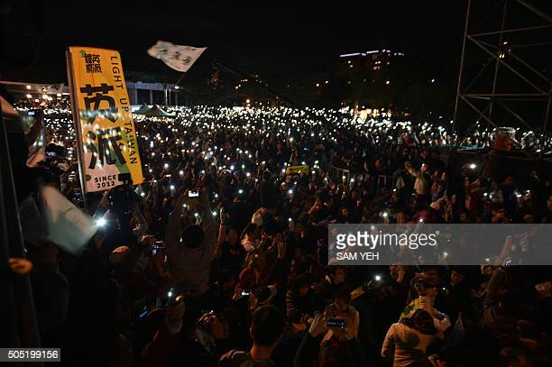 Democratic Progressive Party supporters hold up lights from their mobile phone while gathered outside the party headquarters as they anticipate an...