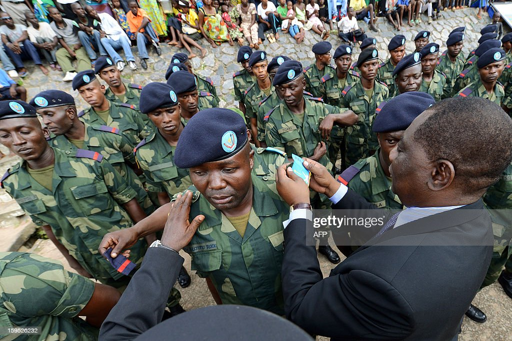 Democratic Republic of Congo Defence Ministger Luba Ntambo awards a soldier during a decoration ceremony for 89 new lieutenants on January 11, 2013 at the central city of Kananga military academy