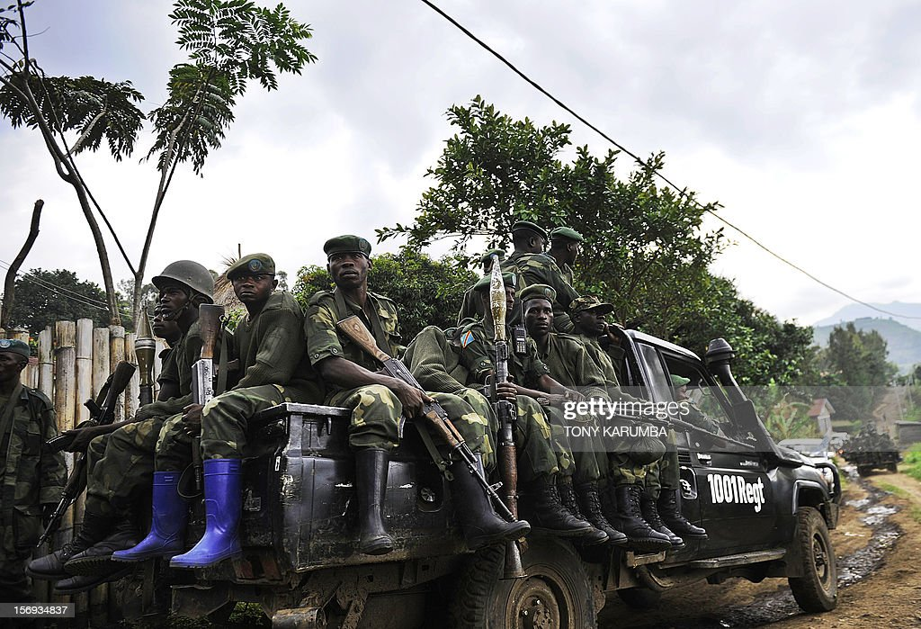 Democratic Republic of Congo government soldiers ride on the back of a truck, on November 25, 2012 in Minova, 70 kilometres south of Goma. Congolese rebels on Sunday rejected demands by regional governments to pull out of the eastern city of Goma to allow for peace talks aimed at preventing a wider conflict and halting a spiralling humanitarian catastrophe.President Joseph Kabila returned to Kinshasa from Kampala 'without meeting anyone from the rebellion' on Sunday despite suggestions of further talks in the Ugandan capital, where he took part in the regional summit. Rwandan President Paul Kagame and his Congo Republic counterpart Denis Sassou-Nguesso called Sunday on both the DR Congo government and rebels threatening to overthrow it to implement regional leaders' call to stop fighting and make peace. AFP PHOTO/Tony KARUMBA