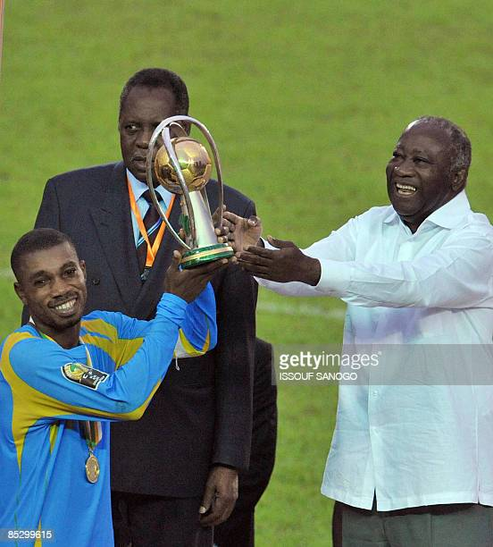 Democratic Republic of Congo national football team captain Gladys Bokese receives the trophy from Ivorian President Laurent Gbagbo and Confederation...