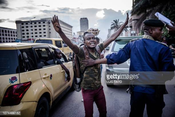 TOPSHOT Democratic Republic of Congo's Police Officer chases away a man as people gather in front of the entrance of the Independent National...