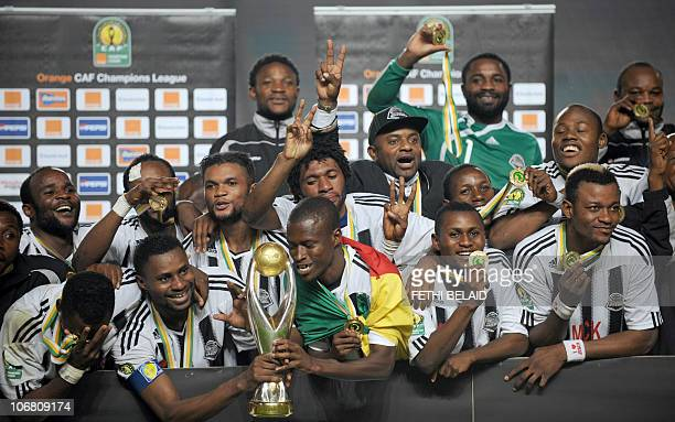 Democratic Republic of Congo's ToutPuissant Mazembe players celebrate with their CAF Champions League trophy after beating Tunisia's Esperance de...