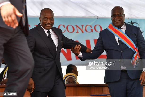 Democratic Republic of the Congo's newly inaugurated President Felix Tshisekedi walks off the podium with outgoing President Joseph Kabila after he...