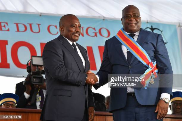 Democratic Republic of the Congo's outgoing President Joseph Kabila shakes hands with newly inaugurated President Felix Tshisekedi on January 24 2019...