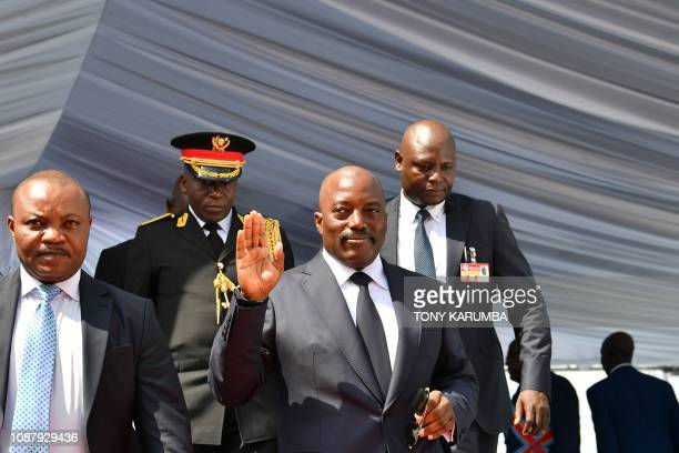 Democratic Republic of the Congo's outgoing President Joseph Kabila waves as he walks off the podium on January 24 2019 after he officially handed...