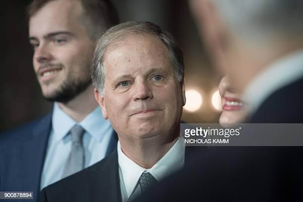 US Democratic Senator from Alabama Doug Jones looks at Vice President Mike Pence at the Capitol in Washington DC on January 3 2018 Jones a civil...