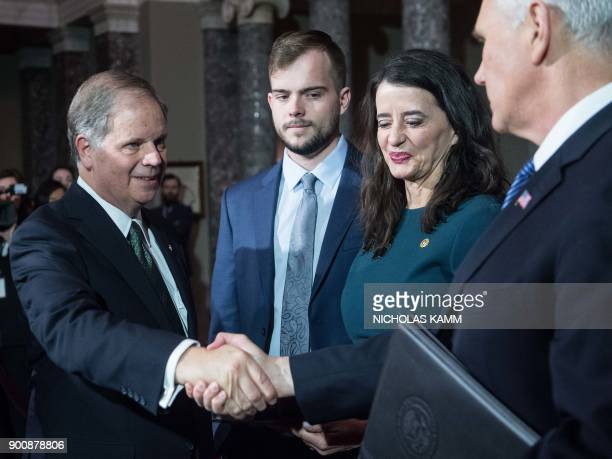 US Democratic Senator from Alabama Doug Jones shakes hands with Vice President Mike Pence at the Capitol in Washington DC on January 3 2018 as wife...